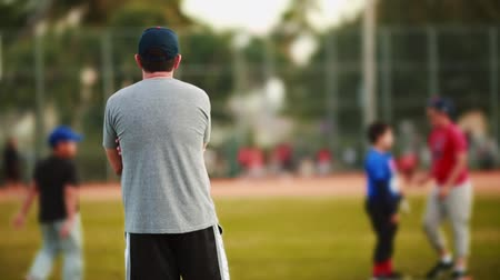 beisebol : Shot from behind of an adult male and unrecognizable kids during baseball practice at field Stock Footage