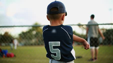 лига : Shot from behind of a cute kid on his baseball uniform stretching his arms behind a fence at baseball park.  He is looking at a coach as he practices with other kids.  Unrecognizable kids and coach practicing Стоковые видеозаписи
