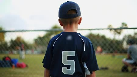 trener : Shot from behind of a cute kid in baseball uniform watching a practice behind a fence at baseball field Wideo