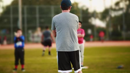 лига : Unrecognizable male coaching kids during practice at a Baseball Field