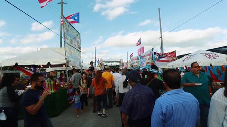 Tilt up of crowd of people at an outdoor festival.  Shot ends showing Puerto Rican flags on a beautiful day.