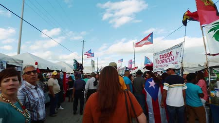Daytime shot as the camera moves in through crowd of people walking around at outdoor festival.  Puerto Rican flags can be seen on the shot.