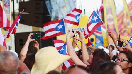 Daytime shot of crowd of people at a festival in front of a stage, taking pictures and holding the Puerto Rican flag.