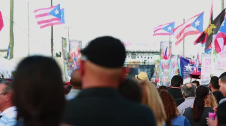 Daytime shot of crowd of people walking around during a festival. Festival was dedicated to Puerto Rico so you can see Puerto Rican flags on the shot.  Shot of the people was taken from behind them and facing a Stage