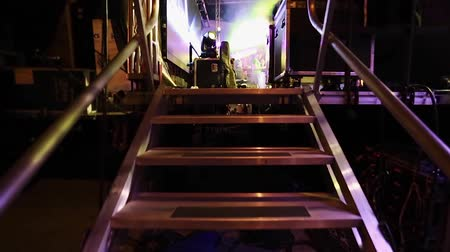 artistas : Subjective shot of an Artist or any other Person walking to a Stage through a stairway during a performance in the evening.  Cool lighting and instruments on top of stage.  Point of View shot Vídeos