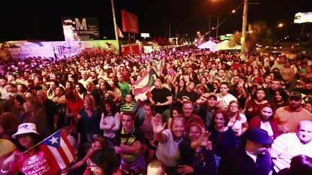 концерт : Pan of big crowd at a festival in the evening hours.  Puerto Rican Flags can be seen on the shot as well as people waving to the camera.