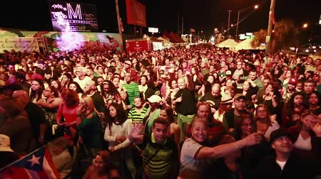 színpad : Tilt up of big crowd at a festival in the evening hours.  Puerto Rican Flags can be seen on the shot as well as people waving to the camera.
