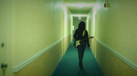 kytara : Female walking down hallway with Electric Guitar on her back
