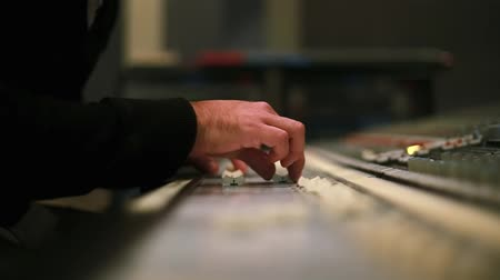 estúdio : Hands of Audio engineer working on a professional analog console, moving faders, mixing music.