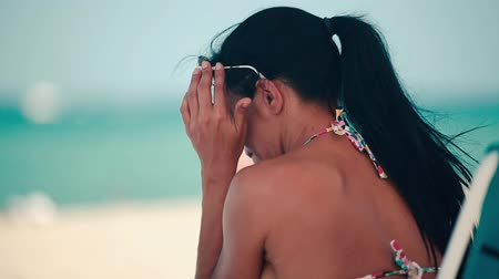 ona : Profile shot of beautiful woman smiling as she enjoys a day at the beach, sitting down, wearing sunglasses and then taking them off, looking towards the ocean. Dostupné videozáznamy