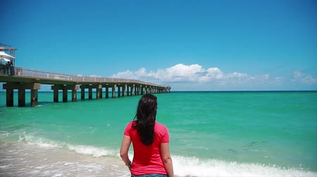 pegada : Really cool and beautiful shot taken from behind of a woman standing in front of the ocean at a beach close to pier in Miami-Sunny Isles