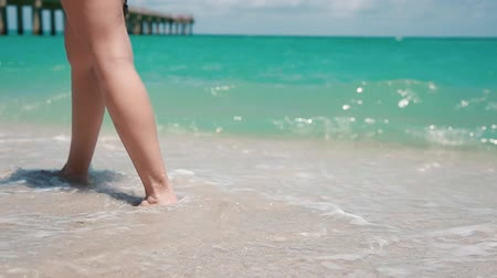 Beautiful daytime shot of a woman walking at beach in Miami-Sunny Isles.  Focus on legs Vídeos