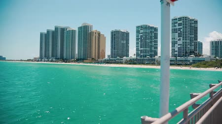 EDITORIALPan of beautiful ocean in Miami-Sunny Isles from the pier towards beach and buildings