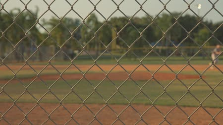 Shot of a baseball field with some players practicing, shot from behind the fence Vídeos