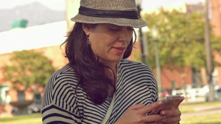 Daytime shot of woman wearing a hat, texting on her cell phone at a park Vídeos