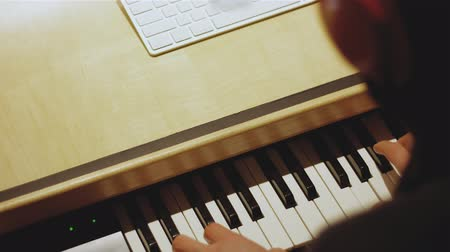 hangszórók : Hands of a music producer while playing a controller keyboard while producing music in a beautiful studio