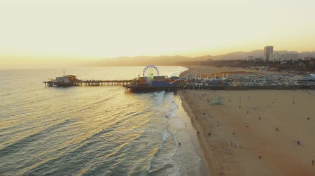 Aerial shot coming out of Santa Monica Pier in California and the ocean during the sunset Vídeos