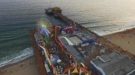 szórakoztatás : Daytime Aerial shot moving out from the ocean and Santa Monica Pier and Rides in California Stock mozgókép