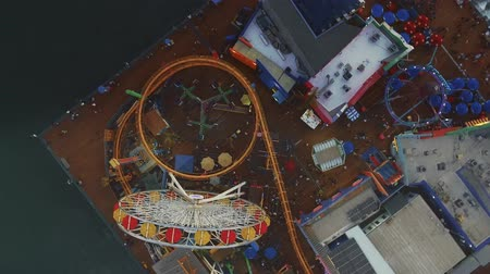 Orbit Aerial shot over moving rides in Santa Monica, Pier in Santa Monica. Shot ends pulling away to show the ocean.