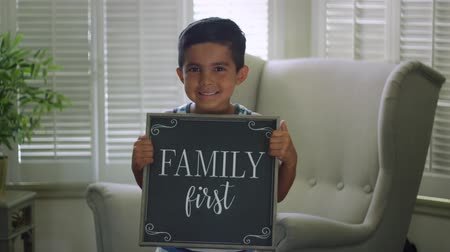 priority : Shot of a little boy holding a sign that says Family First while smiling at the camera
