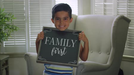 Slow Motion of a little kid looking at the camera while holding a sign that says Family First