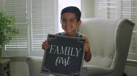 exibindo : Slow motion shot of a little boy holding a sign that says Family First and smiling Stock Footage