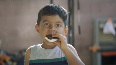 Daytime slow motion of a young boy eating an ice cream sandwich while facing the camera Vídeos