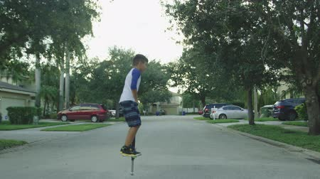 Slow motion shot of a kid jumping on a pogo stick in a rural neighborhood Vídeos
