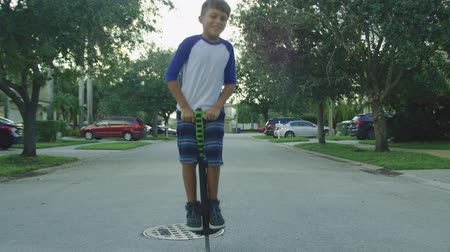 Daytime slow motion shot of a little boy jumping on a pogo stick around homes in a neighborhood Vídeos