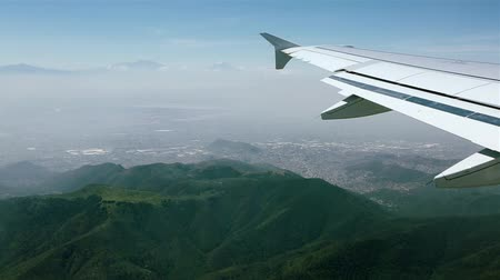 Daytime aerial view from an airplane as it approaches Mexico City. Plane is flying over mountains. Vídeos