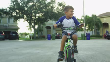 Slow motion shot of young boy riding bike towards the camera while smiling Vídeos