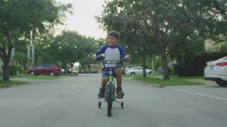 ciclismo : Slow motion of kid riding a four wheel bike around his neighborhood Vídeos