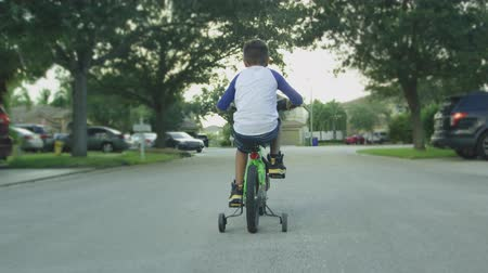 Slow motion shot from behind of kid riding bike in a neighborhood street, surrounded by houses.