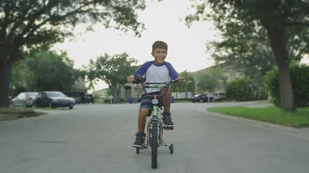 Slow motion of kid riding a bicycle smiling and looking around neighborhood