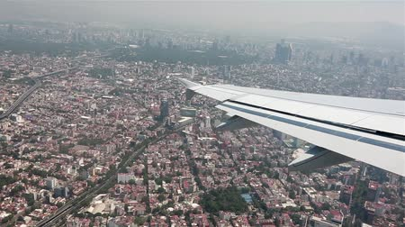 mexico city : Daytime aerial view over Mexico from airplane as it starts to land. Neighborhoods and buildings can be seen in the shot.