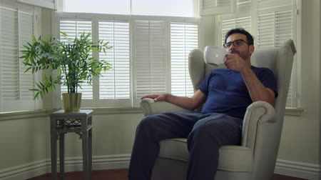 kufel : Slow Motion shot of a man sitting at home, smiling and drinking coffee. Wideo