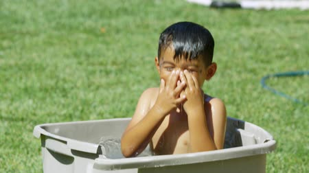 Daytime Slow motion shot of a little boy inside a plastic bin filled with water, using it as a bath or pool. Vídeos