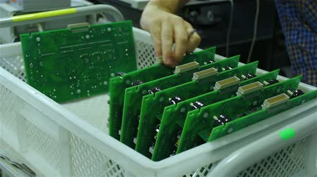 engineering : A worker sorts printed circuit boards Stock Footage