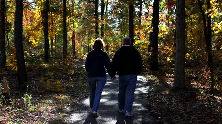 natura : Mature loving couple walk down a pathway in the woods in autumn.