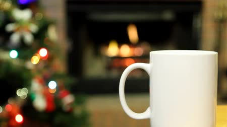 şömine : White mug sits in front of a burning fireplace and Christmas tree into which a hot drink is poured.