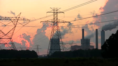 elektrownia : Steam rises from the cooling towers at a nuclear power plant at dusk with electric power transmission lines in the foreground. Wideo