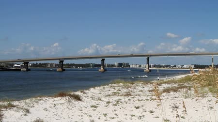 рыболовство : Traffic moves across the inter-coastal waterway on the route 98 bridge at Perdido Pass with dunes and sea oats in the foreground and condominiums in the far background all part of Orange Beach, Alabama.