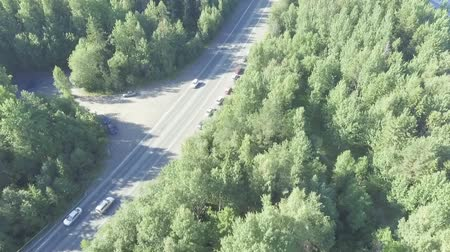 Aerial view of cars traffic on a summer forest highway unsaturated