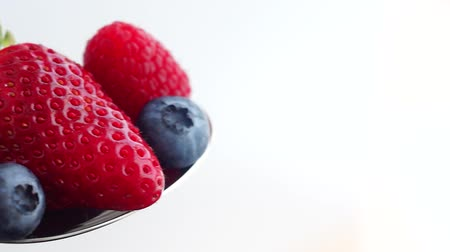 Delicious raspberries, blueberries and strawberries on spoon