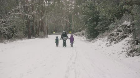 their : Family walking down a snow covered road in the Australian bush