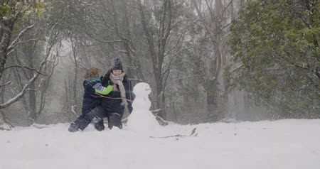 aussie : A mother and son, a woman and a young boy, play in the snow next to a snowman as the snow falls