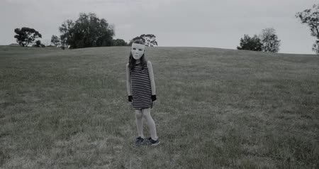 kötülük : Young girl in white halloween mask turns around and then tilts her head to the side in a creepy manner in a park Stok Video