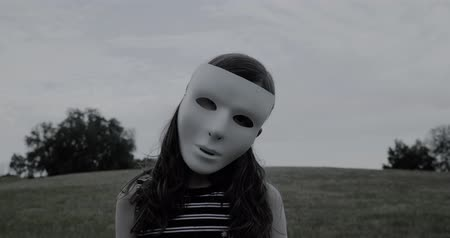 kötülük : Young girl in white halloween mask stands silently and creepily in a park