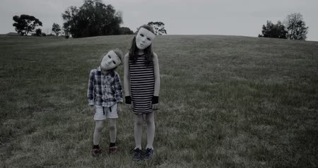 horror : young children wearing a white halloween masks stand creepily and then scarily walk slowly towards the camera Wideo