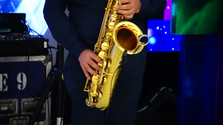 enstrümanlar : Musician is playing on saxophone in concert. Close-up on fingers pressing the keys of the instrument Stok Video